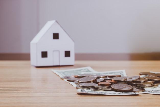 casa-del-papel-y-dinero-en-el-fondo-de-madera_2379-841